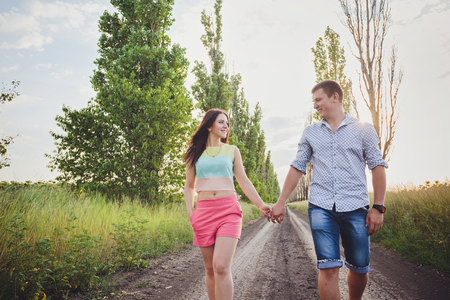sun s: Couple walking holding hands in a park - Romantic date outdoors Stock Photo
