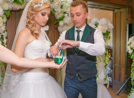 registry: Portrait of handsome groom putting wedding ring on brides hand at registry office