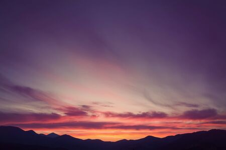 faintly visible: Colorful beautiful sunset over the mountain hills. Retro color.