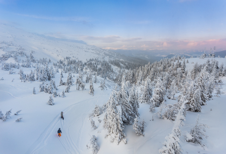 Couple skiing in a groomed curved double ski track with mountain summits and a characteristic cloud formation in the background in the norwegian mountains at easter. Standard-Bild