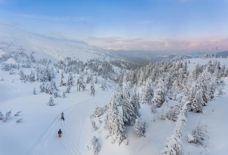 soledad: Pareja esquiando en una pista de esquí de doble curvatura preparado con cumbres de montaña y una formación de nubes característica en el fondo en las montañas noruegas en Pascua.