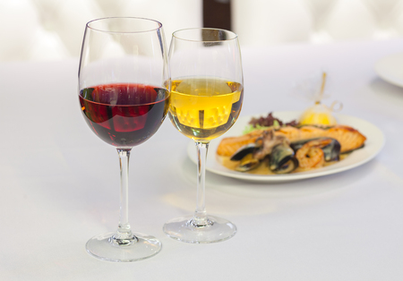 white and red wine in glasses on a background of food