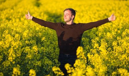 Jeune homme dans le champ de canola jaune se moucher et souffrant d'une allergie au pollen.