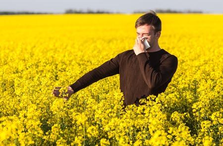 그의 코를 불고 꽃가루 알레르기에서 고통을 노란색 카 놀라 필드에 젊은 남자. 스톡 콘텐츠
