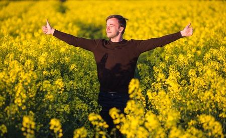Jonge man in geel canolagebied blaast zijn neus en het lijden van pollenallergie. Stockfoto