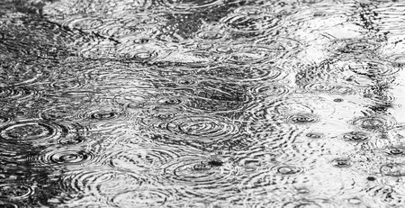 Rain on asphalt or tarmac road creating ripples, high contrast during autumn.