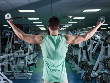 very power athletic guy bodybuilder , execute exercise with dumbbells, in dark gym Stock Photo