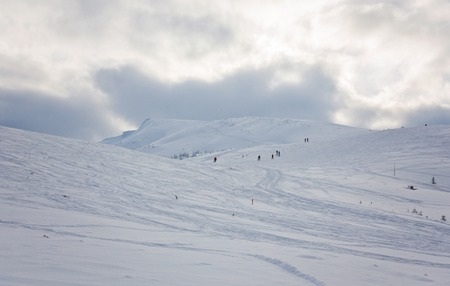 ski track: Couple skiing in a groomed curved double ski track with mountain summits and a characteristic cloud formation in the background in the norwegian mountains at easter. Stock Photo