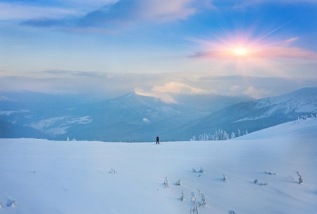 Couple skiing in a groomed curved double ski track with mountain summits and a characteristic cloud formation in the background in the norwegian mountains at easter. Stock Photo