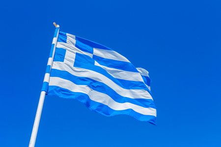 indebtedness: Greek flag in the wind against a blue Summer sky
