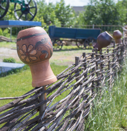 clay jug on wooden fence, take it in Ukraine Stock Photo