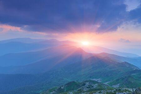 Mooi zomerlandschap in de bergen met de zon bij dageraad Stockfoto