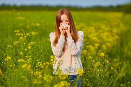 Pollen allergy, girl sneezing in a field of flowers