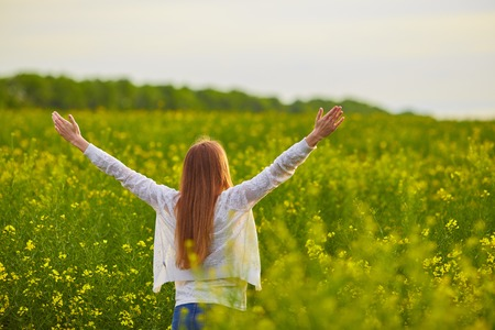 Joyful girl at yellow rape seed meadow