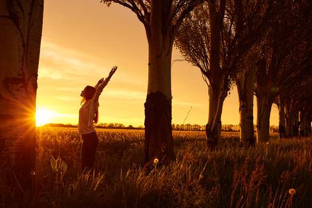 Girl with open arms on a green wheat field in the morning