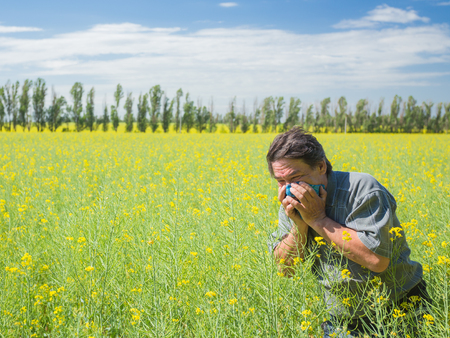 man in field blowing his nose and suffering from hay fever. Stock Photo