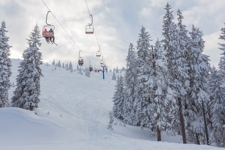 tourism in andorra: Ski lift with seats going over the mountain and paths from skies and snowboards