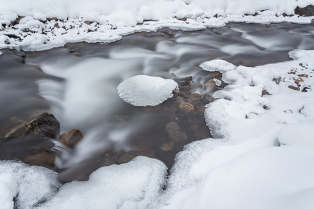 mountain river with big stones in winter time