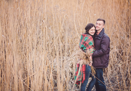 Young couple in love walking in the autumn park near the river. Stock Photo