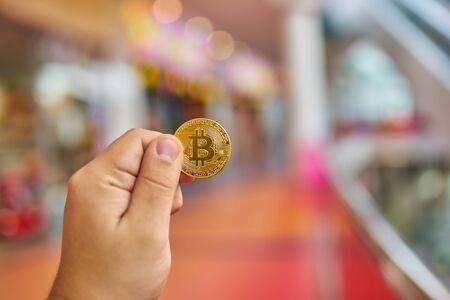 man's: mans hand holding golden Bitcoin on Bitcoin mining background Stock Photo