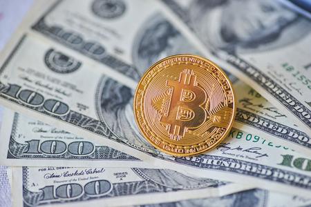 Golden metal bitcoin on dollar bills background