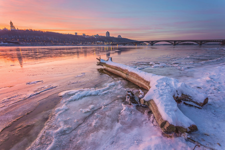 Cold Winter night cityscape with illuminated buildings in Kiev, Ukraine. The frozen Dnieper river appears in the foreground Stock Photo