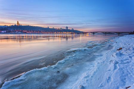 Koude Cityscape van de de winternacht met verlichte gebouwen in Kiev, de Oekraïne. De bevroren rivier de Dnjepr verschijnt op de voorgrond Stockfoto - 91465605