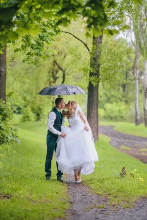 Beautiful bride and groom walking under umbrella at park. Bride with red hair. Newlyweds walking.