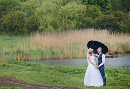 Beautiful bride and groom walking under umbrella at park. Bride with red hair. Newlyweds walking.