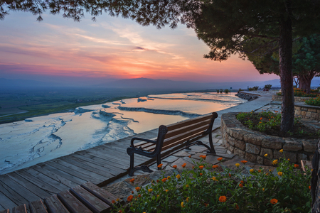 Bank met uitzicht op de Travertijn-zwembaden en terrassen op Pamukkale, Turkije in zonsondergangtijd Stockfoto