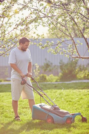 low angle view of young man mowing lawn at home Stock Photo
