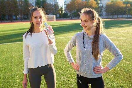 Two sports girls stand and rest after morning exercise.
