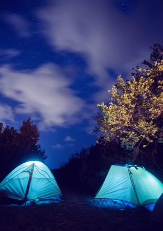 Glowing tent in the mountains under a starry sky Stock Photo