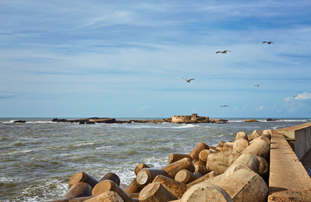 Port of Essaouira in Morocco with local fishing boats, seagulls and fishing nets on a sunny day soft focus Stock Photo