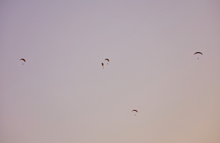 Silhouette Of Paragliders Against Dramatic Sky At Sunset