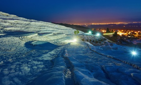 Pamukkale - amazing natural site with white terraces of travertine in Denizli Province, Turkey. Aerial view town of Pamukkale at foot of hot springs and neighborhood in evening.