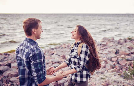 Young couple holding hands by the beach