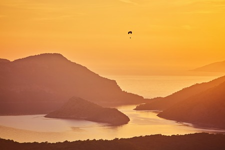 Silhouette of powered paraglider soaring flight over the sea against marvellous orange sunset sky. Paragliding - recreational and competitive adventure sport.