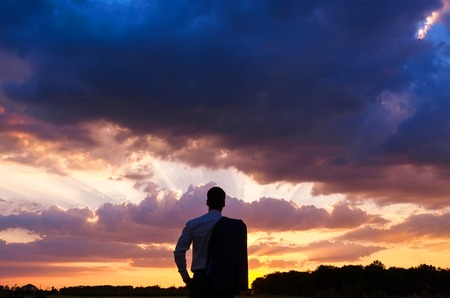 Businessman in elegant suit with his jacket hanging over his shoulder standing in field looking into the distance under a majestic evening sky with a setting sun. Stock Photo