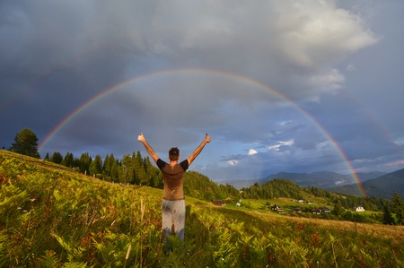 a young guy, a tourist, raised his hands and thumbs up, rejoicing at the seen rainbow