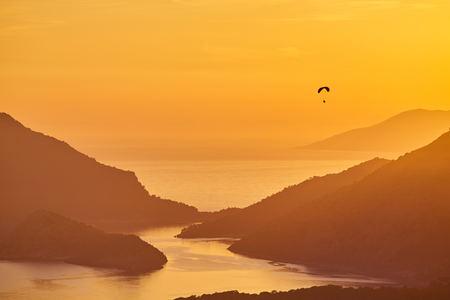 An unidentified paraglider flying at sunset over Blue lagoon in Oludeniz, Turkey 版權商用圖片