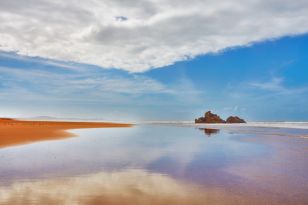 The coast of the Atlantic Ocean, golden sand, blue sky, small rocks are mirrored in the coastal wave. Beach near Esoueira, Morocco
