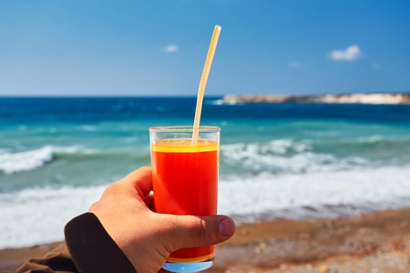 fresh drink in man's hand on the background of the exotic beach close-up