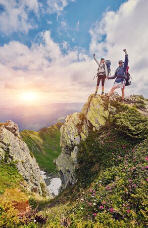 Man and woman standing and hugging on the top of the mountain, autumn hike with backpacks, alpine view