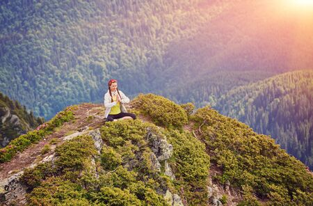 Young girl doing yoga or fitness exercise outdoor in nature with beautiful sky landscape, Namaste pose. Meditation and Relax, freedom concept
