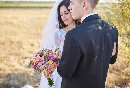 couple in wedding attire with a bouquet of flowers and greenery is in the hands
