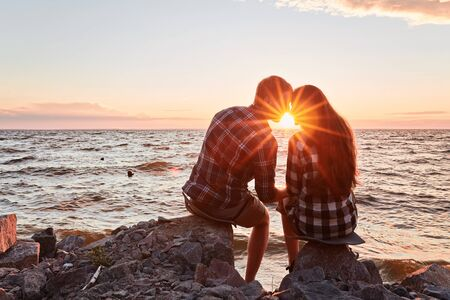 he and she on a nature outing. Romance and love.kiss in the sunset sun Foto de archivo