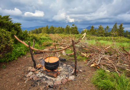 Old small kettle is heated on a bonfire on a green mountain meadow during a bad weather. Epic travel in the mountains. Stockfoto