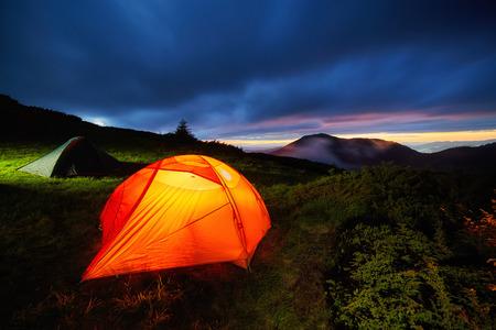 Gele verlichte tent in de Beautirul Evening Mountains. Avontuur en reisconcept.