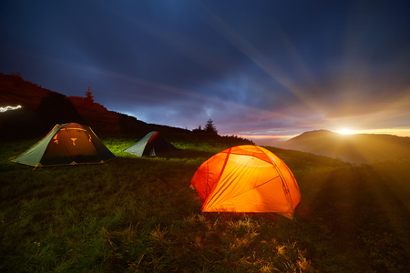 Tenda illuminata gialla nelle montagne serali di Beautirul. Avventura e concetto di viaggio.